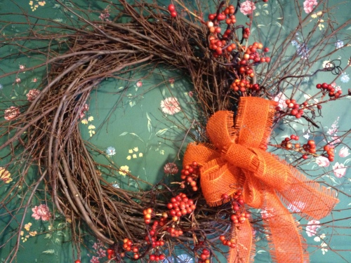 Twiggy wreath decorated with berries and burlap bow